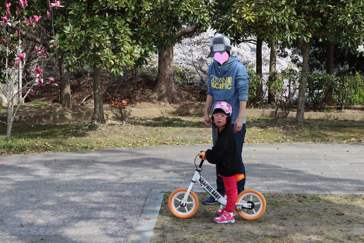 バランスバイクに乗るダウン症の娘